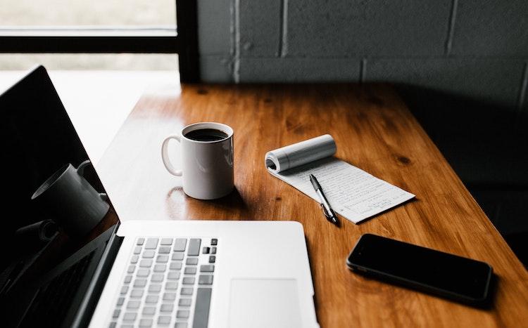 számítógép, tol, füzet, telefon és bögre egy asztalon