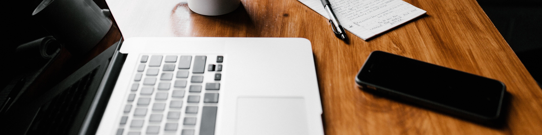 asztalon laptop, füzet és tol és telefon